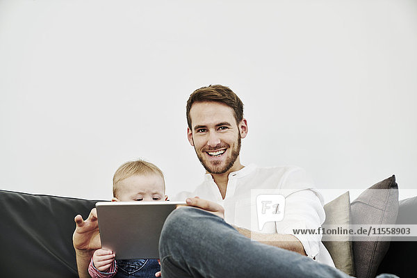 Vater mit Mädchen mit Tablette auf der Couch