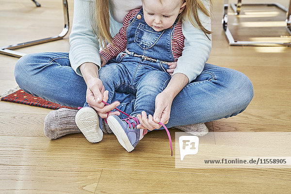 Mutter und Baby sitzen auf dem Boden und binden Schuhe.