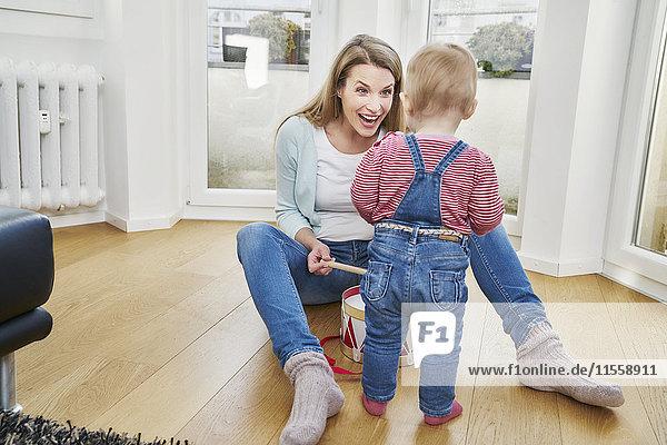 Glückliche Mutter und kleines Mädchen beim Schlagzeug spielen zu Hause