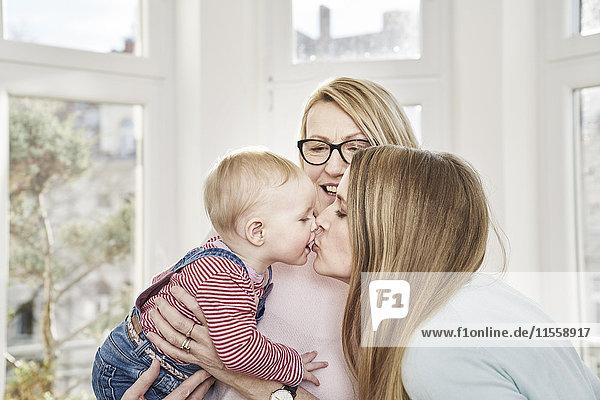 Mädchen wird von Großmutter gehalten  die ihre Mutter küsst.