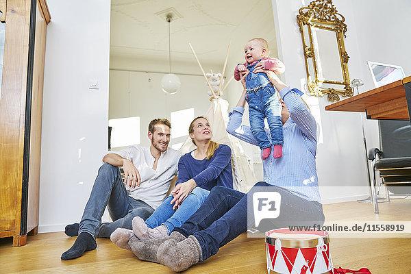 Glückliche Familie mit einem kleinen Mädchen im Wohnzimmer