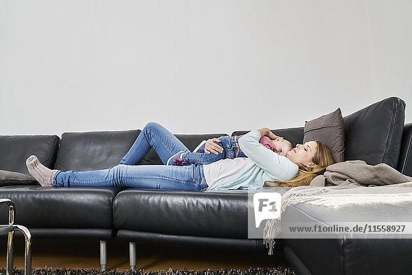 Mutter und kleines Mädchen auf der Couch liegend