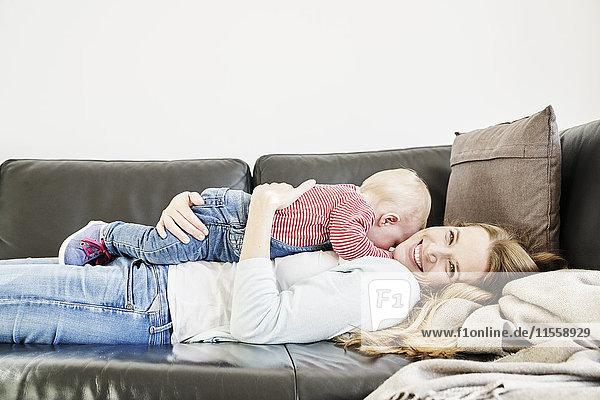 Glückliche Mutter und kleines Mädchen auf der Couch liegend