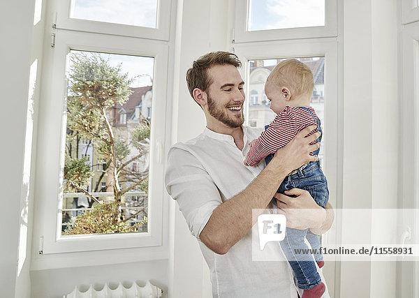 Vater hält kleines Mädchen am Fenster