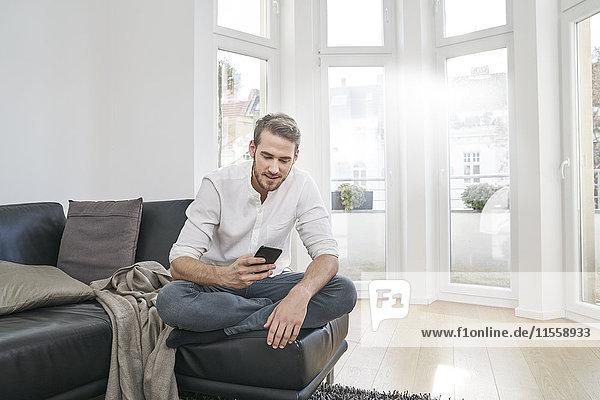 Mann sitzt auf der Couch und schaut auf sein Handy.