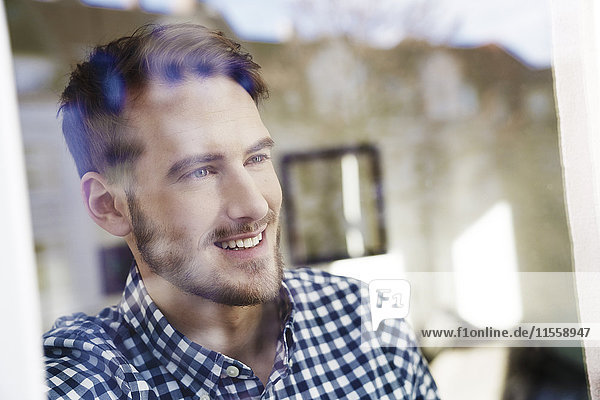 Lächelnder Mann schaut aus dem Fenster