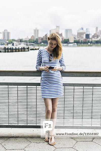 USA  New York City  Junge Frau steht in Manhattan mit Smartphone
