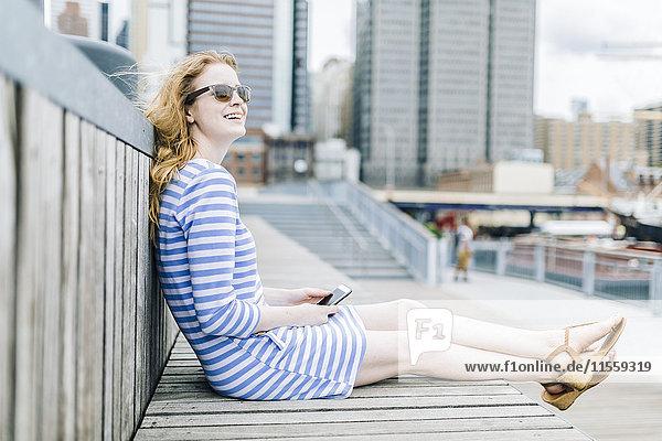 Junge Frau am Pier sitzend mit dem Handy