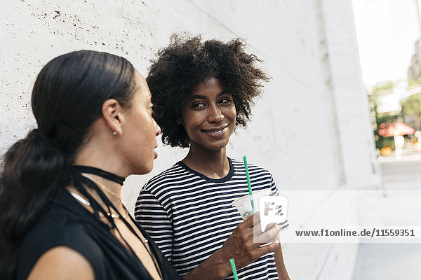 Portrait of smiling woman with drink listening to her friend