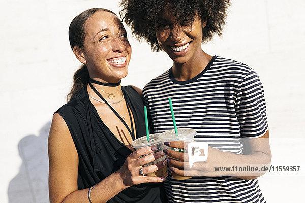 Zwei lachende Frauen stoßen mit Getränken in Plastikbechern an.