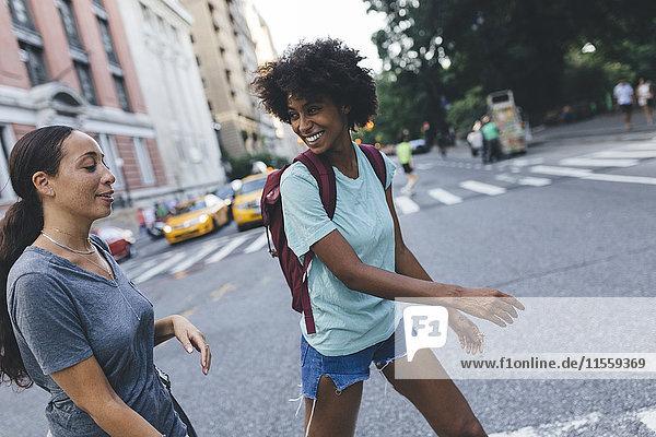 USA  New York City  zwei Freunde überqueren die Straße