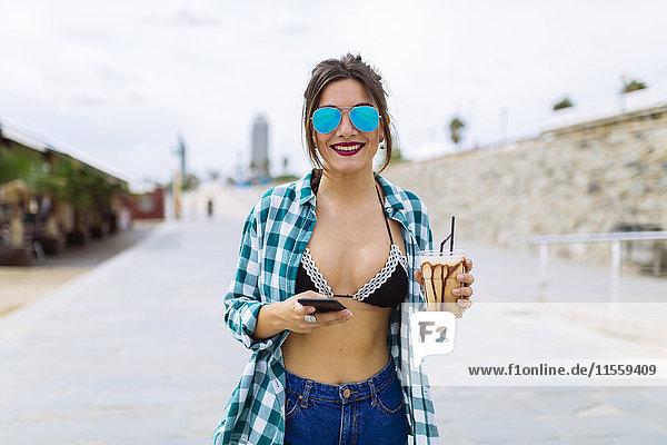 Junge Frau am Strand mit Tasse Kaffee und Smartphone