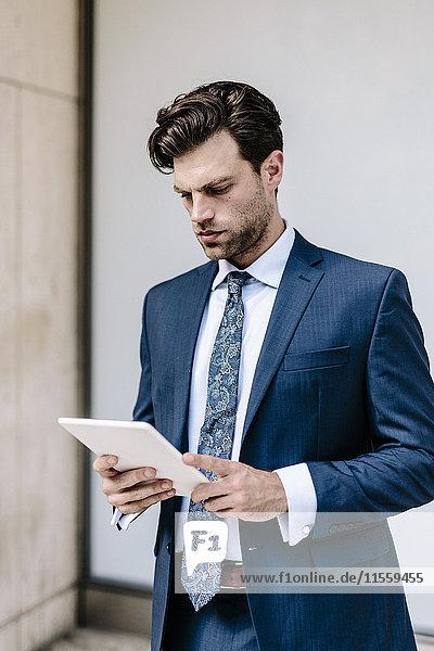 Gutaussehender Geschäftsmann mit digitalem Tablett
