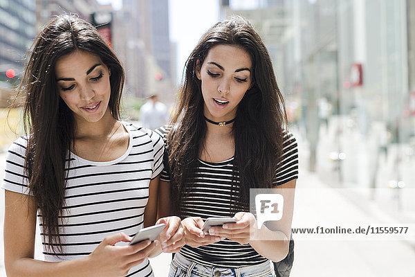 USA  New York City  zwei Zwillingsschwestern beim Blick auf Handys in Manhattan