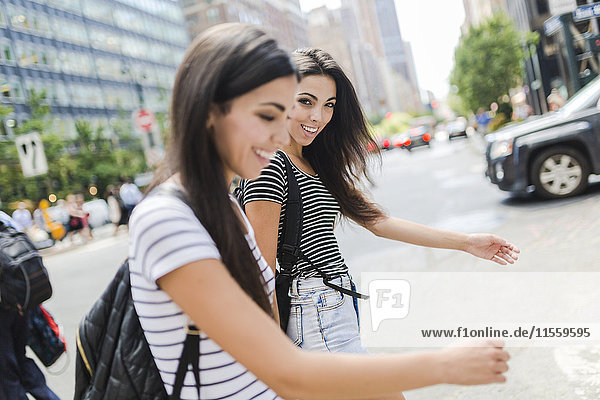 USA  New York City  two happy twin sisters on the go in Manhattan