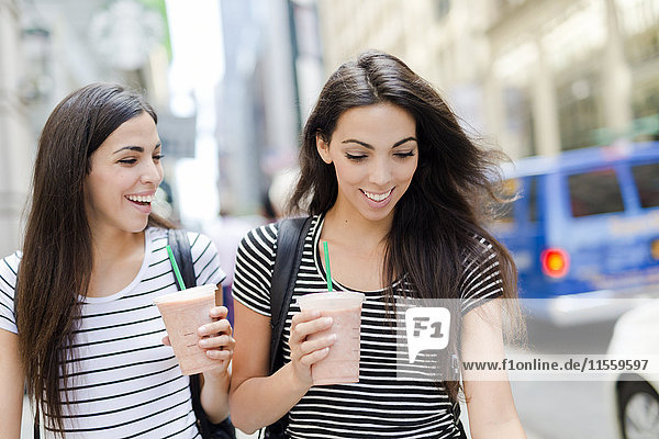 USA  New York City  two happy twin sisters on the go in Manhattan with takeaway drink