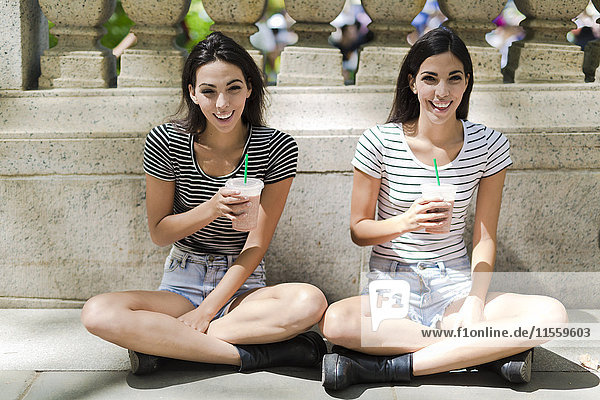 Zwei glückliche Zwillingsschwestern sitzen im Freien und trinken etwas zum Mitnehmen.
