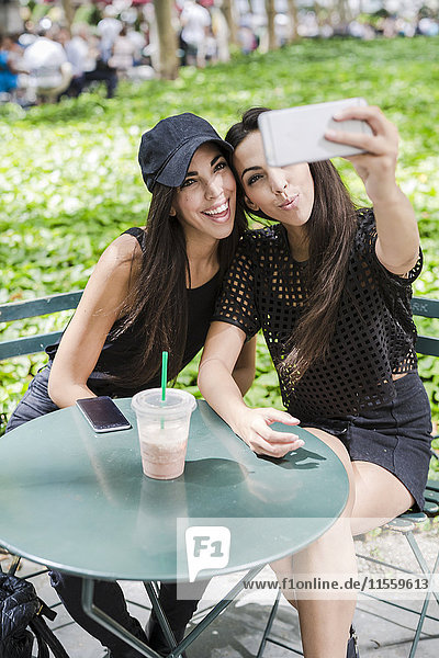 Zwei Zwillingsschwestern  die einen Selfie bei Tisch im Park nehmen.