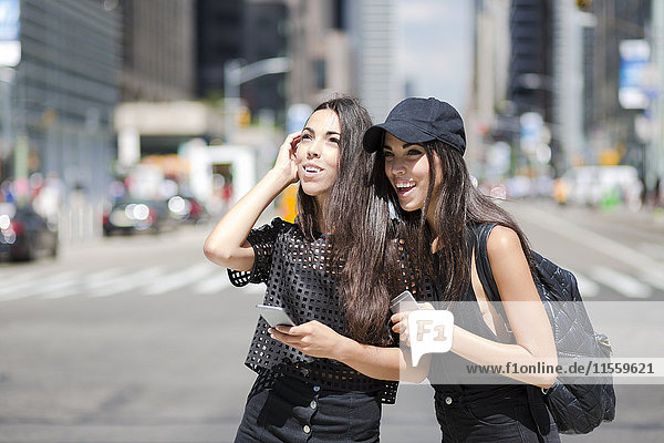 USA  New York City  two happy twin sisters with cell phones in Manhattan