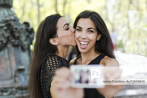 Zwei glückliche Zwillingsschwestern mit einem Sofortfoto