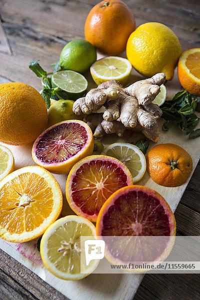 Geschnittene und ganze Zitronen  Orangen und Limetten  Ingwerwurzel und Minzblätter auf Holzbrettchen Geschnittene und ganze Zitronen, Orangen und Limetten, Ingwerwurzel und Minzblätter auf Holzbrettchen