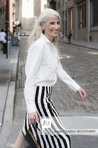 USA  Brooklyn  Porträt einer lächelnden reifen Frau auf der Straße