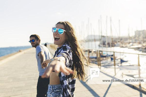 Glückliches junges Paar beim Spaziergang am Hafen