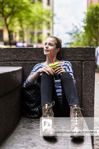USA  New York City  Frau macht eine Pause und trinkt einen Smoothie in Manhattan.