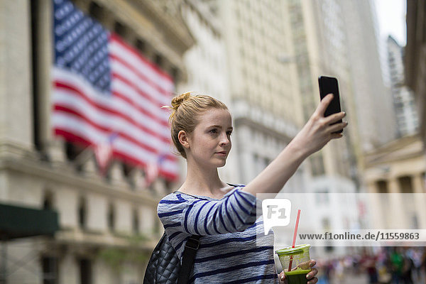 USA  New York City  woman taking selfie in front of New York Stock Exchange