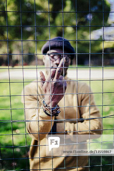 Mann hinter einem Metallnetz mit dem Finger