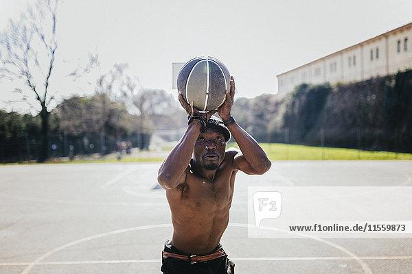 Barechested Basketballspieler auf dem Platz werfen Ball