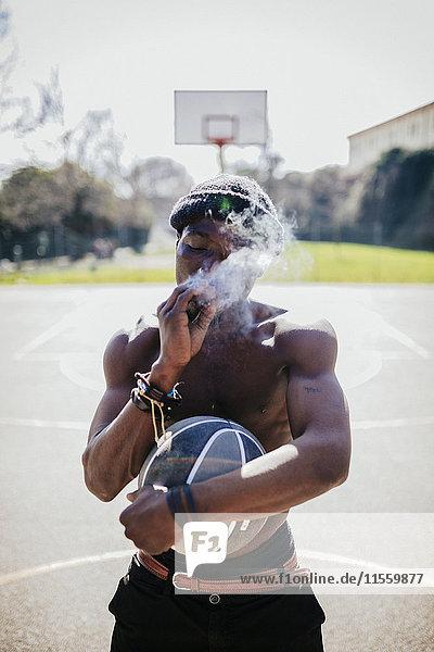 Barechested Basketballspieler auf dem Platz Rauchen ein Joint
