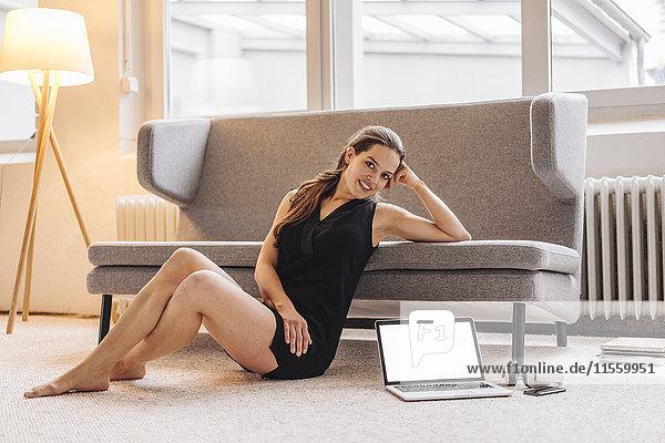 Porträt einer lächelnden Frau auf der Couch neben dem Laptop