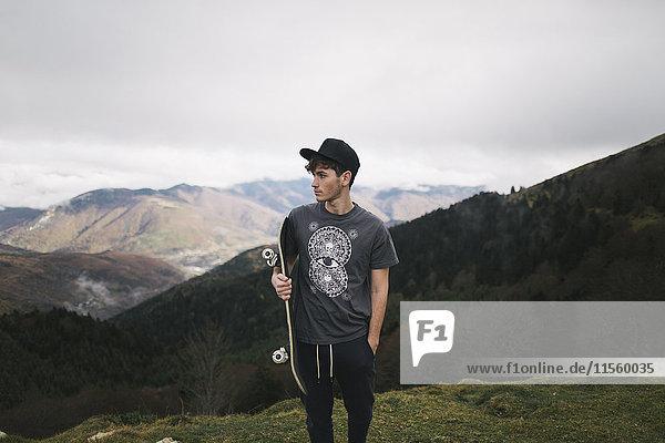 Spanien  Lleida  junger Mann mit Skateboard in ländlicher Landschaft