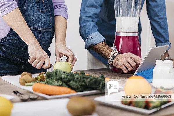 Hände eines Paares  das Früchte zubereitet und eine Tablette zur Zubereitung von Smoothies verwendet