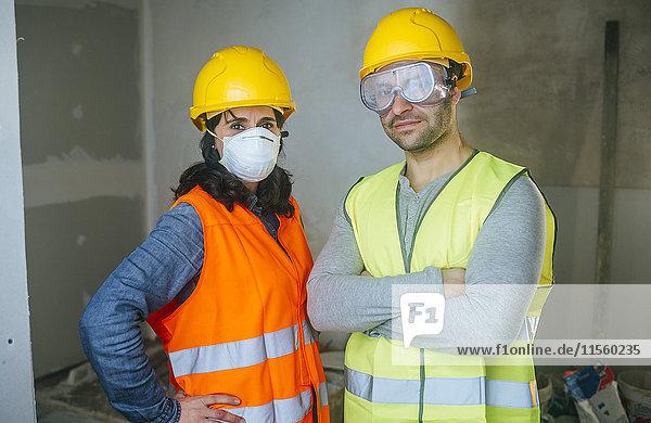 Porträt einer Frau mit Maske und eines Mannes mit Schutzbrille auf einer Baustelle