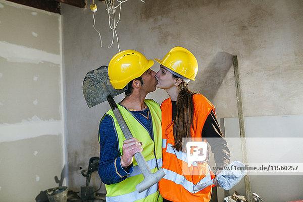 Paar in Arbeitskleidung  das sich auf einer Baustelle küsst