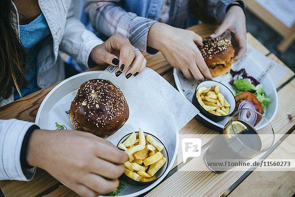 Frauenhände essen Hamburger und Pommes frites