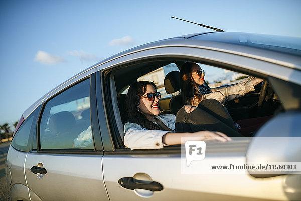 Zwei junge Frauen  die in einem Auto unterwegs sind.