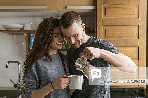Liebespaar in der Küche stehend  Kaffee trinkend