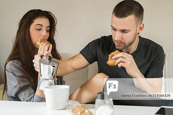Amorous couple sitting on couch  having breakfast