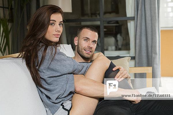Liebespaar auf der Couch sitzend  umarmend