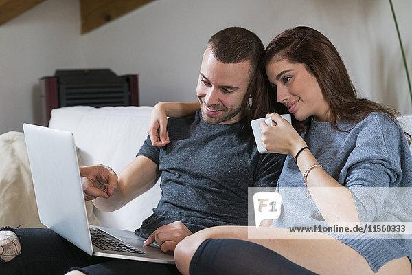 Junges Paar auf der Couch sitzend mit Laptop