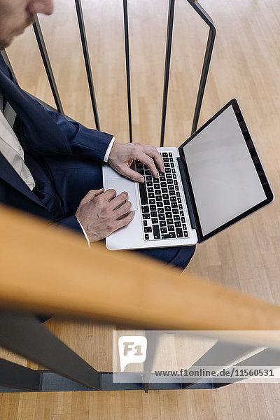 Geschäftsmann auf der Treppe sitzend mit Laptop