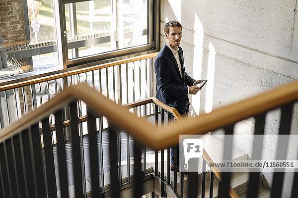 Geschäftsmann mit Tablette im Treppenhaus