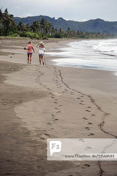 Indonesia  Java  back view of two women walking on the beach