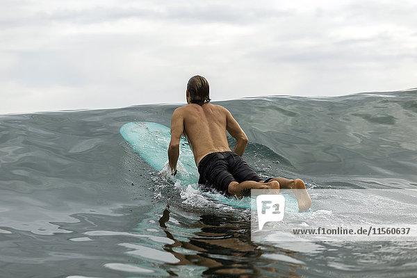 Indonesien  Java  Mann auf dem Surfbrett auf dem Meer liegend