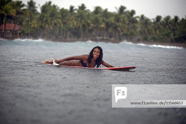 Indonesien  Java  Frau auf dem Surfbrett auf dem Meer im Regen liegend