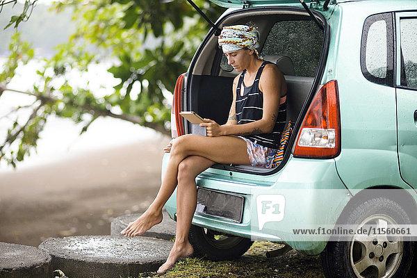 Indonesien  Java  Frau im Kofferraum eines Autos mit Tablette