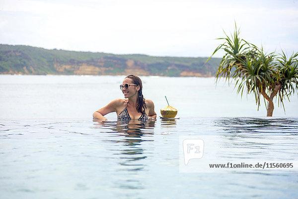 Indonesien  Insel Lombok  lächelnde Frau im unendlichen Pool